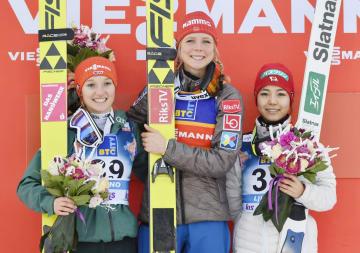 3位になり表彰台で笑顔の高梨沙羅(右)。中央は今季7勝目を挙げたマーレン・ルンビ=リュブノ(共同)