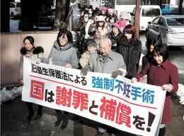 国の謝罪と補償を求める横断幕を掲げ、提訴に向かう弁護団ら=30日午前10時30分ごろ、仙台地裁前