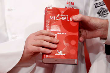 発表イベントでシェフが手にする2018年のフランス版「ミシュラン」=5日(ロイター=共同)