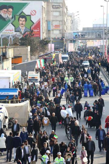 11日、イラン革命39年の記念集会で、街頭を行進する参加者=テヘラン(共同)