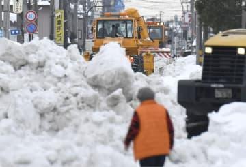 福井県坂井市の国道8号に続く道路で続けられる除雪作業=12日