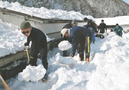 雪に埋もれた家を掘り出すように作業に取り組む参加者