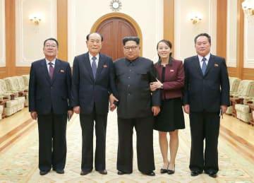 12日、韓国から帰還した北朝鮮の金与正朝鮮労働党第1副部長(右から2人目)ら高官代表団と記念写真に納まる金正恩党委員長(中央)。労働新聞が13日掲載した(コリアメディア提供・共同)