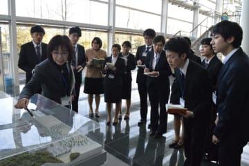 宮崎日日新聞社が開いたインターンシップの取材体験で、県産業振興機構の職員から話を聞く学生=13日午後、宮崎市佐土原町