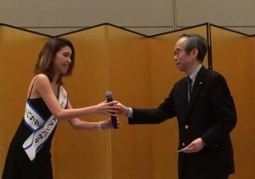 イブニングパーティーで、挨拶をした鈴木真二理事長からマイクを受け取るSaasha。約600人の参加者が歌声に酔った=2018年2月8日、東京ビッグサイト