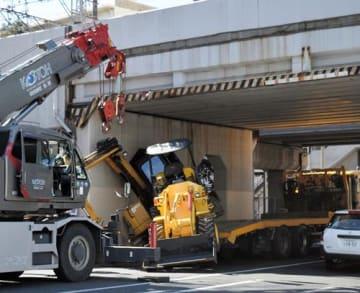 トラックの荷台から落下した小型重機(写真中央)=13日午前10時50分ごろ、千葉市中央区本千葉