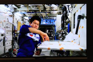 宇宙での実験を披露する金井宣茂さんの中継映像