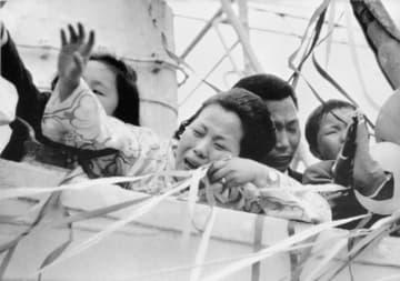 北朝鮮に向け新潟港を出港する船上で、泣きながら手を振る帰還者=1971年5月