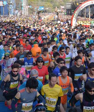 フルマラソンの部でスタートする市民ランナーたち=18日午前9時3分、熊本市中央区のびぷれす熊日会館前(高見伸)