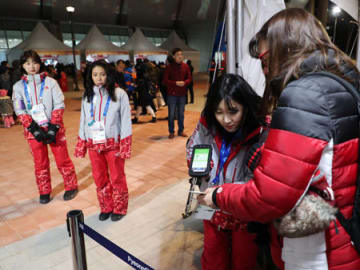 スピードスケート会場の入り口で来場者のチケットを確認する京都外国語大の李さん(江陵)