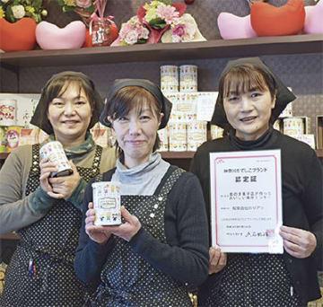 有加里さん(右)とクッキー缶を手にする女性スタッフたち