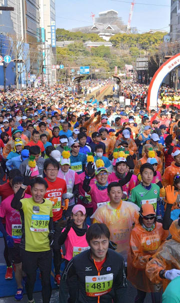 熊本城をバックに、フルマラソンの部でスタートする市民ランナーたち=18日午前9時すぎ、熊本市中央区(高見伸)