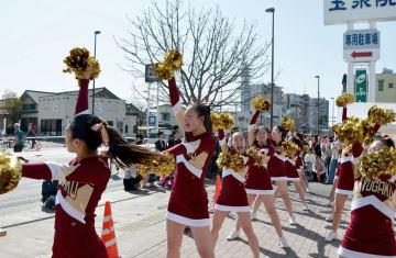 チアリーディングで沿道を盛り上げる九州学院チアダンス部員ら=18日、熊本市中央区