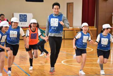 松田さん(中央)と鬼ごっこなどを通じて交流する児童たち