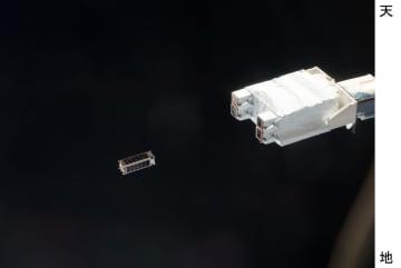国際宇宙ステーションの日本実験棟「きぼう」の装置(右)から放出される超小型衛星=2017年1月(JAXA、NASA提供)