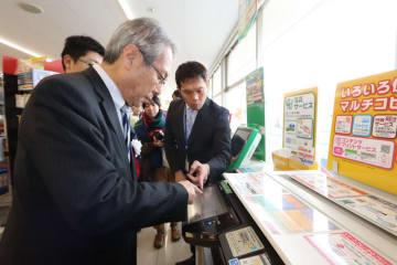 住民票の写しを取得するためマルチコピー機を操作する杉澤市長(手前)=西海市、ファミリーマート西海樫浦店