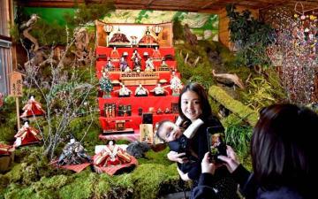 雛山をバックに記念写真を撮る家族連れ=24日午後、綾町南俣の飲食店「おの屋」