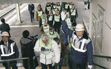 JR職員に誘導され、ホームから改札口に向かう訓練参加者