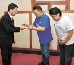 村井知事に小切手を手渡す伊達さん(中央)と富沢さん(右)