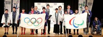 本県入りしたオリンピックとパラリンピックのフラッグ。井上康生さん(後列左から2人目)、城島茂さん(同3人目)から県内の児童・生徒らが受け取った=3日午後、宮崎市・県立芸術劇場