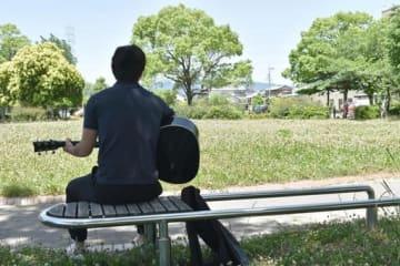 公園で趣味のギターを弾く加藤哲郎=愛知県西部、2017年6月4日