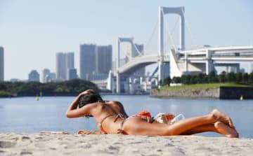ビーチで日光浴する女性=2016年、東京・お台場