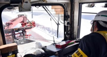 運転席から角度や高さを慎重に見ながら雪を切り崩す作業員