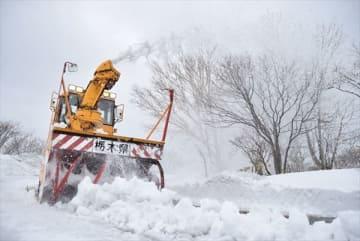 路上に積もった雪をかき込み、勢い良く吹き上げて除雪する作業車
