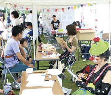 福島県新地町の祭りで似顔絵を描く杉山さん(右)