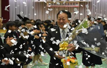 紙吹雪が舞う花道を通る草間典夫校長=常総市本石下の石下中学校