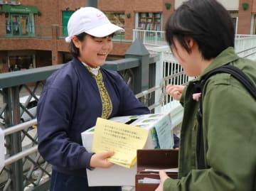 募金活動に励む安野さん(左)=長崎市、JR長崎駅前高架広場