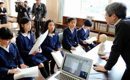 ロボットとの会話に挑戦する児童たちに助言する平田オリザさん=豊岡市中陰、五荘小学校