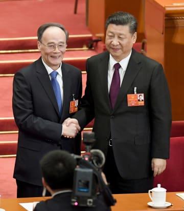 中国全人代の全体会議で副主席に選出された王岐山氏(左)と握手する習近平国家主席=17日、北京の人民大会堂(共同)