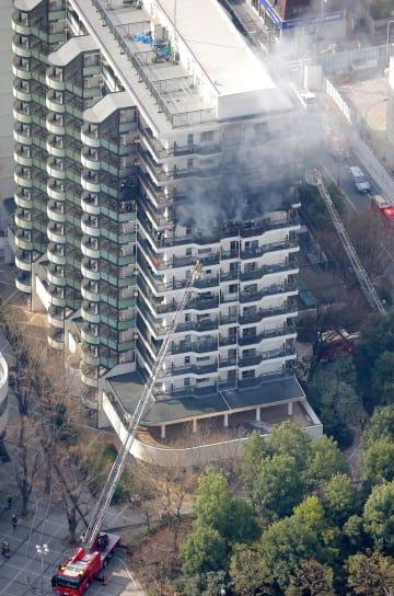 火災で煙を上げる川崎市高津区のマンション=18日午前(共同通信社ヘリから)