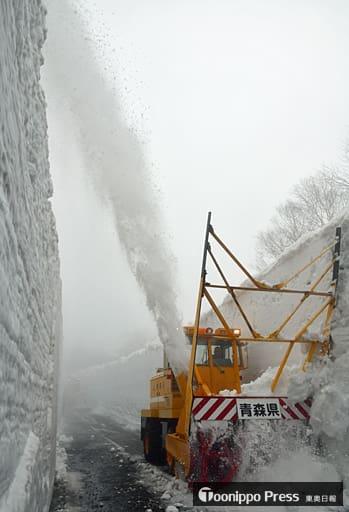 ガスが立ち込める中、壁を削った雪を高く吹き飛ばしながら進むロータリー除雪車=14日午前、八甲田・十和田ゴールドライン
