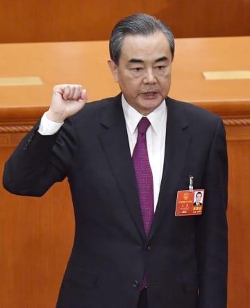 中国全人代で国務委員兼外相に選出され、宣誓する王毅氏=19日、北京の人民大会堂(共同)