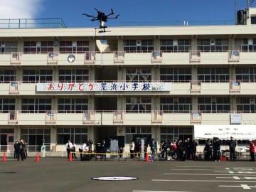 閉校して震災遺構となっている旧荒浜小学校の校舎を背景に浮上するドローン