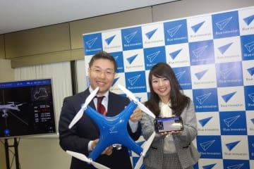 AEEドローンを手にするブルーイノベーション株式会社の熊田貴之代表取締役社長(左)
