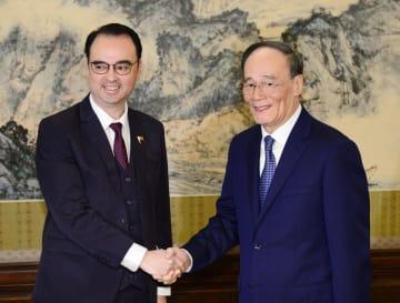 会談を前に握手する中国の王岐山国家副主席(右)とフィリピンのカエタノ外相=23日、北京の中南海(共同)
