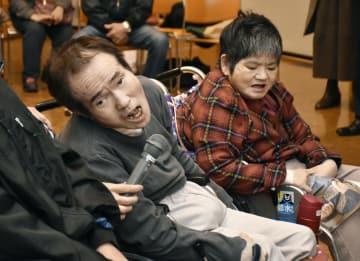 石牟礼道子さんの遺影の前で話す半永一光さん(左)=24日午後、熊本県水俣市