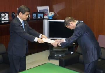 石井国交相(左)から業務改善指示書を受け取る日産の西川広人社長=26日午前、国交省