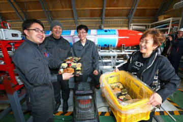 IST実験場に、特製のカツ弁当を届けた青山さん(右)。「みんなを信じている」と力強く語った=27日午前、阿部裕貴撮影