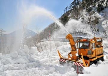積雪を吹き上げて進む除雪車=28日午前、日光市湯元