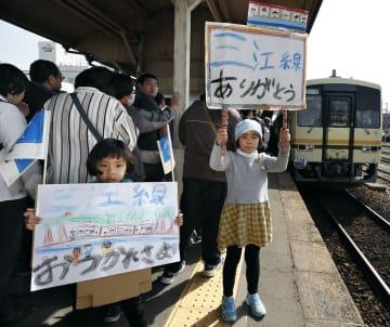 JR三江線の運行最終日を迎え、三次駅でメッセージを掲げる女の子=31日午前、広島県三次市