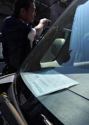 駐車禁止除外指定車標章を載せた車を調べる捜査員=神戸市兵庫区