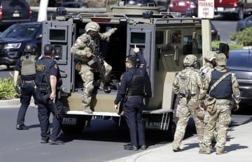 3日、「ユーチューブ」本社前で装甲車両から降りる武装した警察官ら=米カリフォルニア州サンブルーノ(AP=共同)