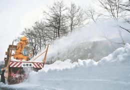ごう音を響かせながら雪の壁を削る除雪車