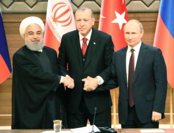 4日、トルコの首都アンカラで会談後、共同記者会見の会場で手を握る(左から)イランのロウハニ、トルコのエルドアン、ロシアのプーチンの各大統領(共同)