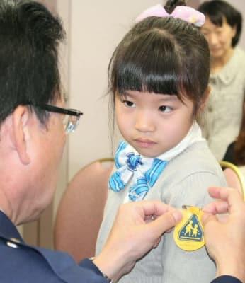 左肩に黄色いワッペンを着けてもらう金池小の新1年生=4日、県庁