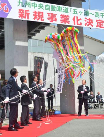 くす玉を割り、九州中央自動車道の新規事業化を祝う参加者たち